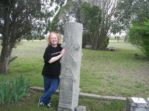 The distinctive Woodmen of the World tombstone of George M. Lock (1880-1912) is highlighted by HCHC's Linda Coker at Martin Church Cemetery.