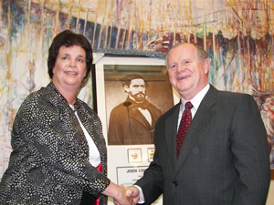 HCHC Chair Kate Johnson and San Francisco Sheriff Michael Hennessey share a happy moment and congratulatory handshake following the Texans' presentation to the sheriff of a framed photo of Jack C. Hays, complete with the representative badges Hays once wore with distinction.